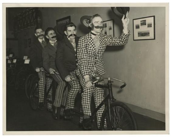 Photograph of four men on a bicycle built for four. They are all wearing fake(?) mustaches and have checked trousers. The man in front is wearing a checked jacket. 1936. Philadelphia Record Photograph Morgue [V04].